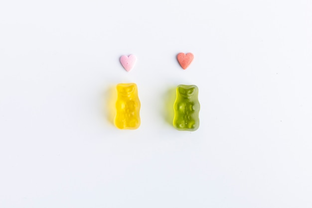 Romantic gummy bears with hearts on the head on white background