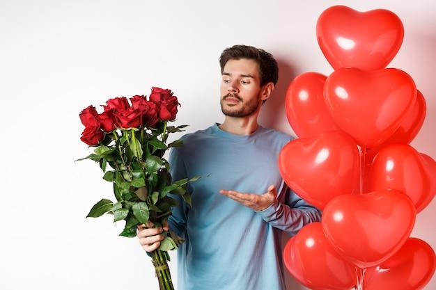 赤いバラの花束を見せて、花を指して、バレンタインデーにハートの風船の近くに立っているロマンチックな男は、彼の恋人、白い背景への贈り物を準備します