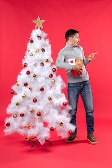 飾られた白いクリスマスツリーの近くに立って、赤に驚いて彼の贈り物を持っているロマンチックなハンサムな大人