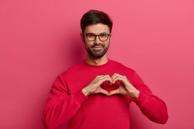 로맨틱 잘 생긴 수염 난 남자는 손가락으로 하트 모양 기호를 만든다.