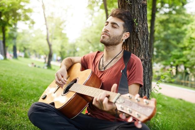 楽器のある公園で休んでロマンチックなハンサムな男。ミュージシャンは草の上に座るとギターを弾く