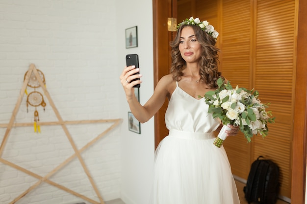 Romantic and happy caucasian bride in stylish wedding dress taking selfie