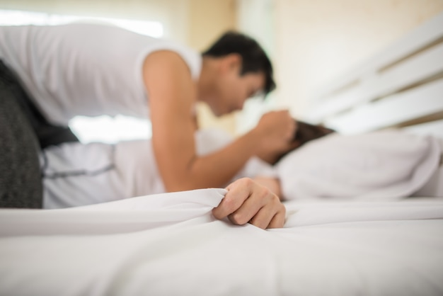 Romantic happy couple in bed enjoying sensual foreplay.