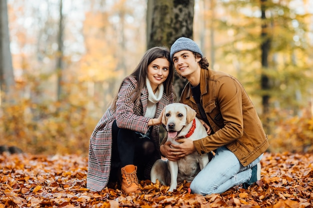 秋の公園でラブラドールとの時間を楽しんで恋にロマンチックな幸せなカップル