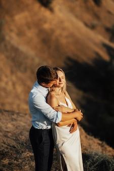 愛のロマンチックな幸せなカップルは抱擁し、夕方の日光で時間を過ごします。