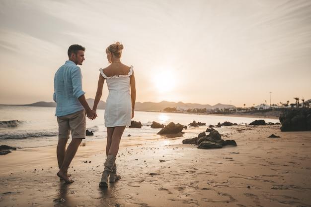 夕暮れ時のビーチで歩く愛のロマンチックな幸せなカップル。