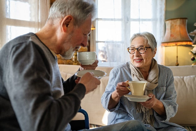 Romantic happy senior couple in love at home. mature man with disability in wheelchair having fun with wife