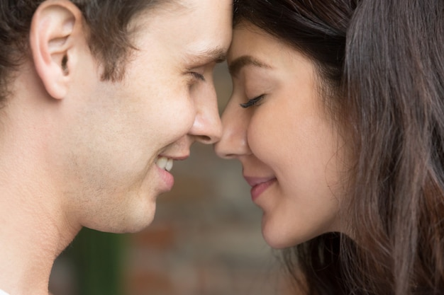 Romantic happy sincere couple face to face close up portrait