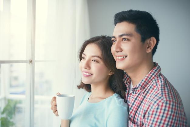 Романтичная счастливая молодая азиатская пара расслабляется в современном доме в помещении