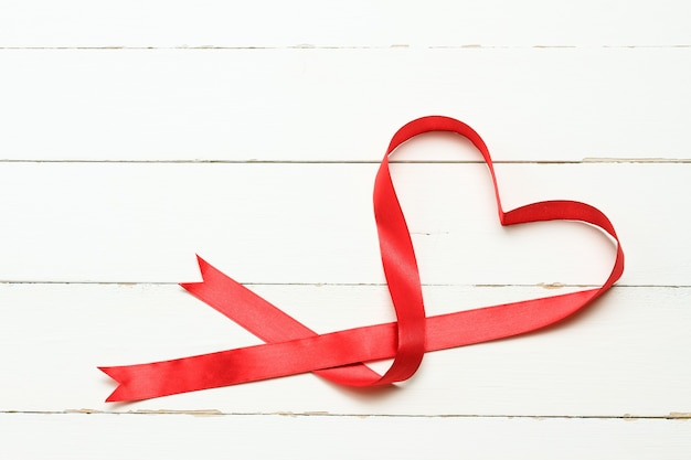 Romantic heart shaped ribbon over white wooden background