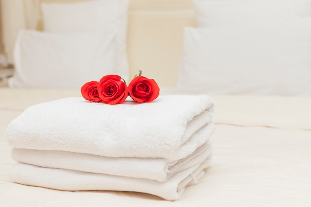 Romantic holiday with red roses on white towels
