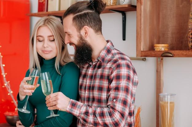 Романтический домашний праздник. бородатый парень пьет шампанское со своей девушкой на кухне