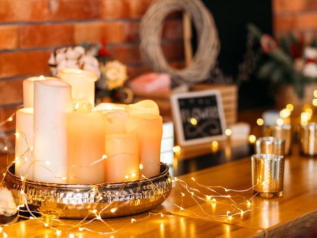 낭만적 인 가정 장식. 흐림 벽돌 벽 위에 요정 조명과 촛불의 배열.