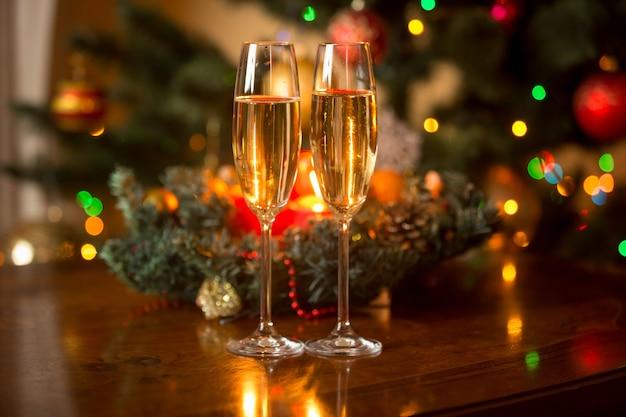샴페인 두 잔과 나무 테이블에 촛불이 있는 크리스마스 화환의 낭만적인 이미지