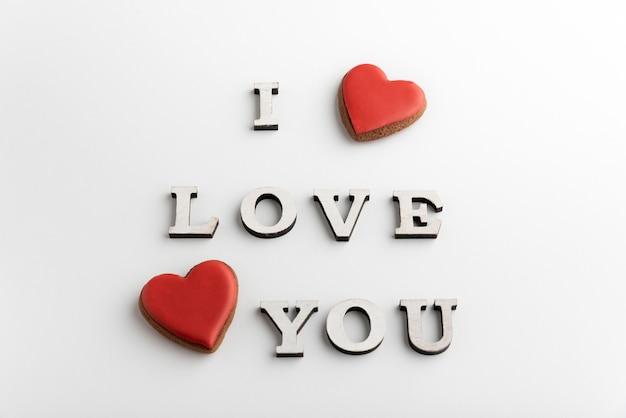 Романтическая надпись i love you и пряники в форме сердца на белой поверхности. день святого валентина.