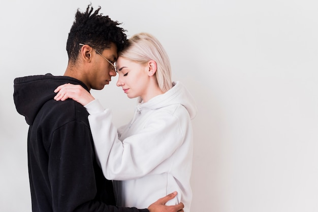 Romantic interracial young couple against white background