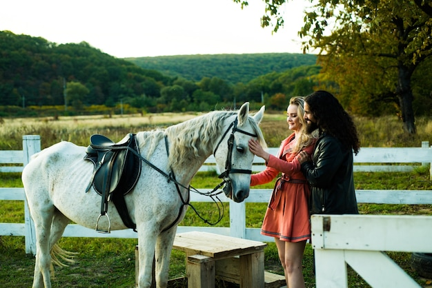 Romantic joyful couple with horse flirting and playing. young lovers riding horses.