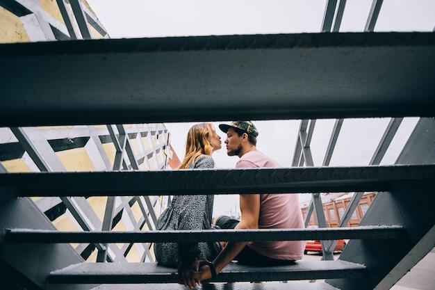 Романтический поцелуй двух влюбленных в городе / молодая счастливая пара