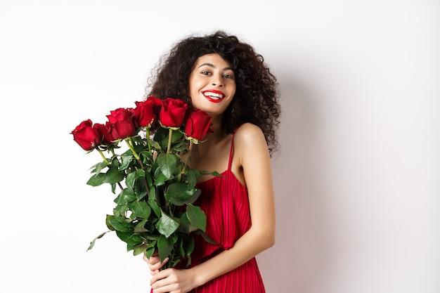 巻き毛とファッショナブルなドレス、赤いバラの花束を持って笑顔、白い背景の上に幸せに立っているロマンチックな女性。