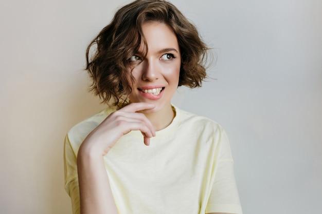 光の壁にふざけてポーズをとってロマンチックな笑いの女の子。巻き毛の夢のような魅力的な女性モデルの屋内肖像画。