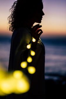 서있는 여자와 노란 전구 빛으로 낭만적 인 생활 개념