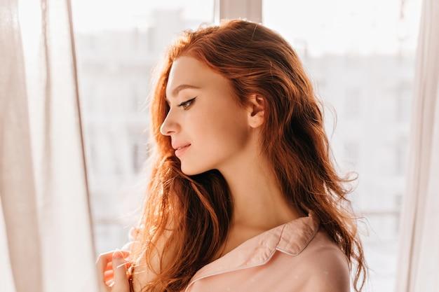 Romantica signora dai capelli lunghi in posa a casa. ritratto della ragazza attraente pensierosa dello zenzero.