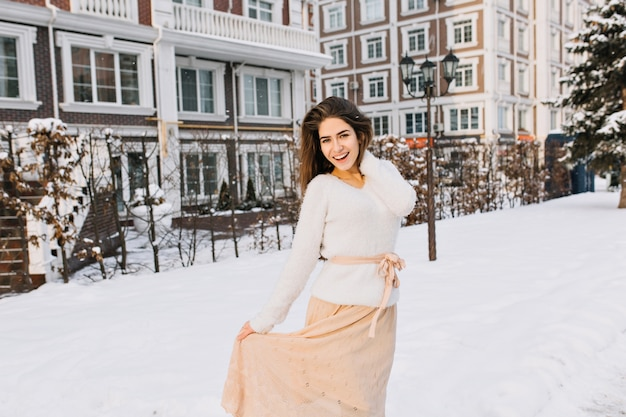 Romantic long-haired woman in skirt posing on the street full of snow with lantern. outdoor portrait of smiling shy woman in white sweater having fun in cold winter day.