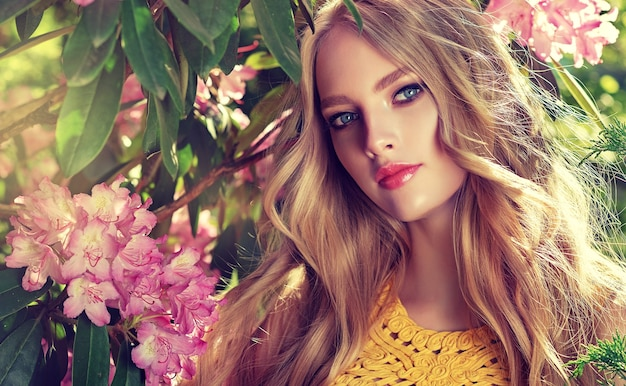 Romantic look of beautiful blue eyes of young woman surrounded by blooming garden flower trees. freely curling long blonde hair, elegant makeup with rose lips. blossom of youth.