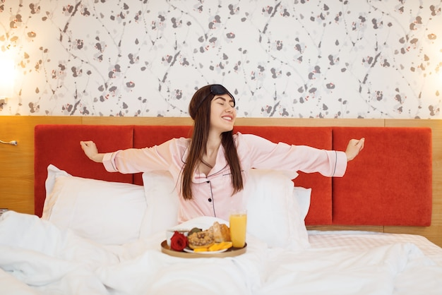 ロマンチックな愛のカップル、自宅のベッドでバラと朝食をとっている幸せな妻、おはよう、思いやりのある夫。家族の調和のとれた関係