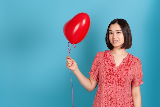 Romantic, in love young asian woman in red dress and dark hair holding a flying red heart shaped balloon