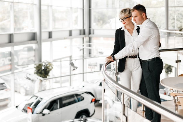 Romantic lovely couple standing hugging in interior of dealership.