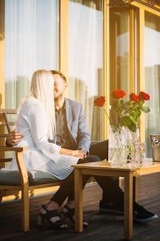 パティオに座っているロマンチックな素敵な若いカップル
