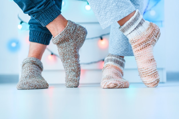 Romantic lovers family couple in warm knitted soft cozy socks in wintertime at home