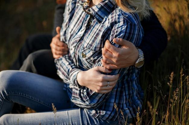 Романтические влюбленные сидят на траве и обнимаются