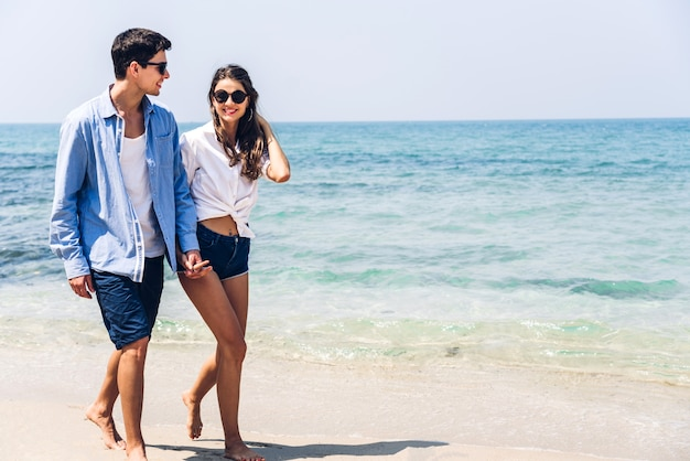 熱帯のビーチで一緒にリラックスして歩いて手を繋いでいるロマンチックな恋人の若いカップル。