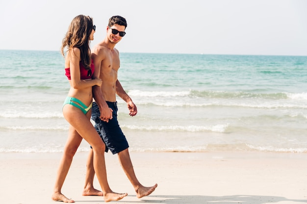 Romantic lovers young couple holding hands walking relaxing together on the tropical beach. summer vacations