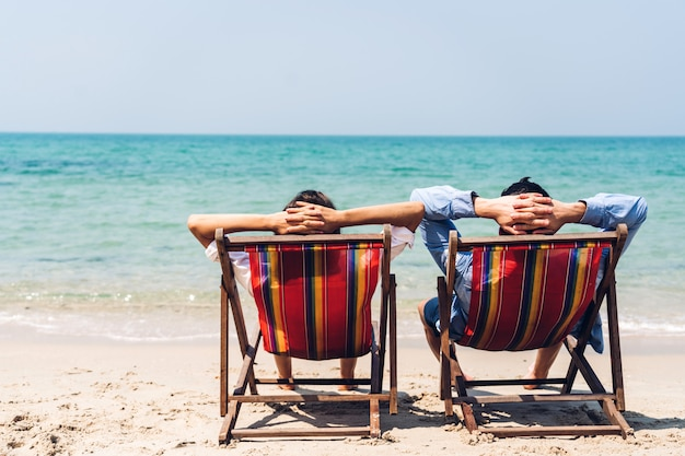 Romantic lovers young couple relaxing sitting together on the tropical beach and looking to the sea.summer vacations