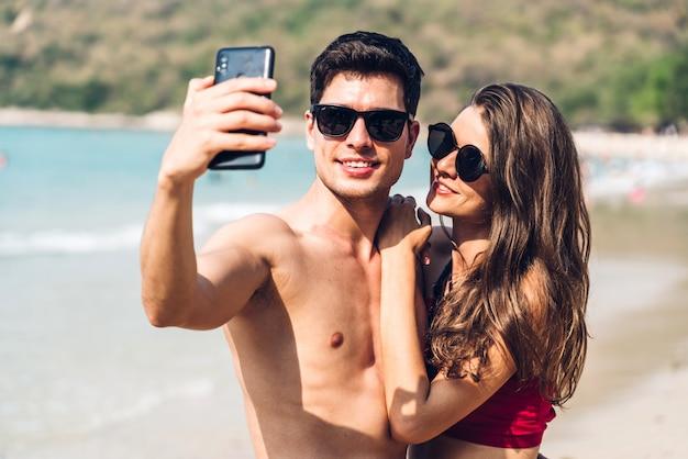 Романтические влюбленные молодая пара, расслабляющаяся вместе на тропическом пляже. мужчина и женщина, делающие селфи со смартфоном и наслаждающиеся жизнью. летние каникулы
