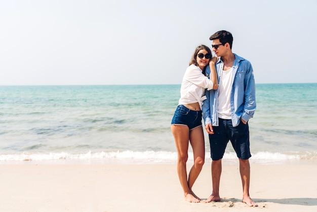 熱帯のビーチで一緒にリラックスしたロマンチックな恋人の若いカップル。