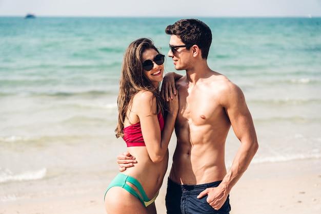 熱帯のビーチで一緒にリラックスしたロマンチックな恋人の若いカップル。男は女性とハグし、人生を楽しみます。夏休み
