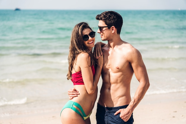Romantic lovers young couple relaxing together on the tropical beach. man hugging with woman and enjoy life. summer vacations
