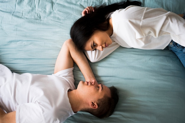 Romantic loving couple lying on bed and looking into eyes