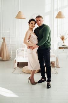 ロマンチックな愛情のある若いカップル、赤ちゃんを期待している将来の両親。居心地の良い寝室で妊娠中の妻を抱きしめる男。 。高品質の写真