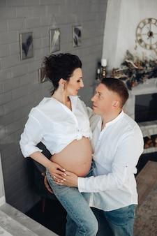 ロマンチックな愛情のある若いカップル、赤ちゃんを期待している将来の両親。居心地の良い家のインテリアで裸の腹を持つ妊娠中の妻を抱きしめる男。高品質の写真
