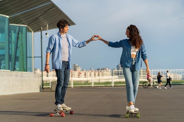 ロマンチックな男性と女性が手をつないでロングボードに乗って指で心を示しています。屋外で恋をしているかわいいトレンディなカップルは、スケートボードでのデートの関係活動を楽しんでいます。アーバンライフスタイルとファッションコンセプト