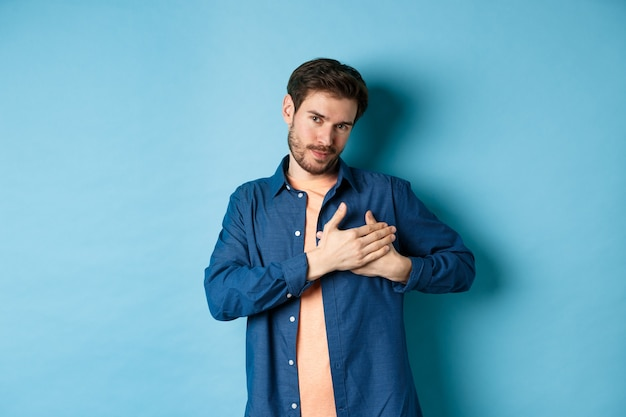 Romantic man holding hands on heart and smiling, thanking you, standing grateful on blue background.