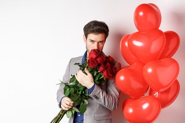 ロマンチックな男は赤いバラの花束を嗅ぎ、カメラを情熱的に見ています。バレンタインデーに行くスーツのボーイフレンドは、ギフトとハートの風船、白い背景でデートします。