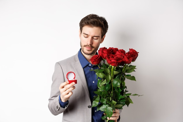 Romantic man in suit looking pensive at engagement ring, going to make a marriage proposal on valentines day, holding bouquet of roses, standing over white background.