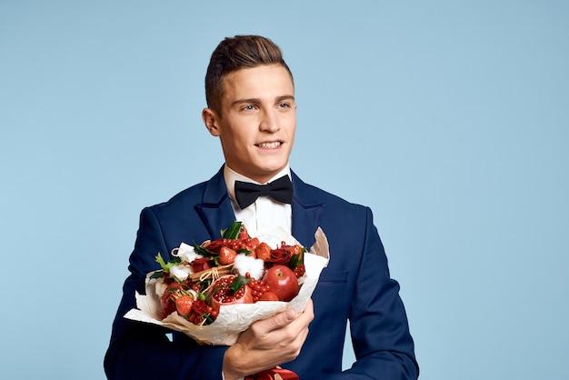 Романтический мужчина с букетом цветов и в галстуке-бабочке на синем фоне обрезанный вид. фото высокого качества