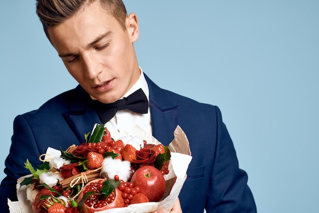 Романтичный мужчина с букетом цветов и в галстуке-бабочке на синем
